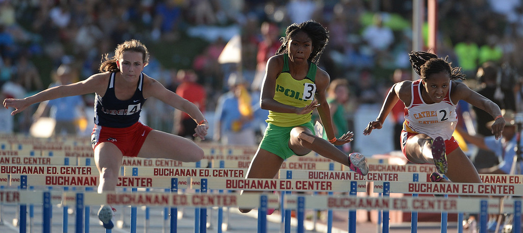 Description of . Long Beach Poly's Kymber Payne, center, competes in the 100 meter hurdles competes in the during the CIF California State Track & Field Championships at Veteran's Memorial Stadium on the campus of Buchanan High School in Clovis, Calif., on Saturday, June 7, 2014.   (Keith Birmingham/Pasadena Star-News)