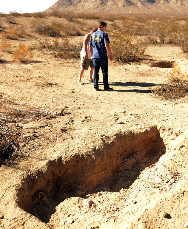 Description of . Joel Myers,51, left, and Allen Gadban,20 both of Adelanto looks at the multiple grave sites  Thursday November 14, 2013 where skeletal remains were found in shallow graves Tuesday November 12, near Victorville west of the 15 Freeway. LaFonzo Carter/ Staff Photographer