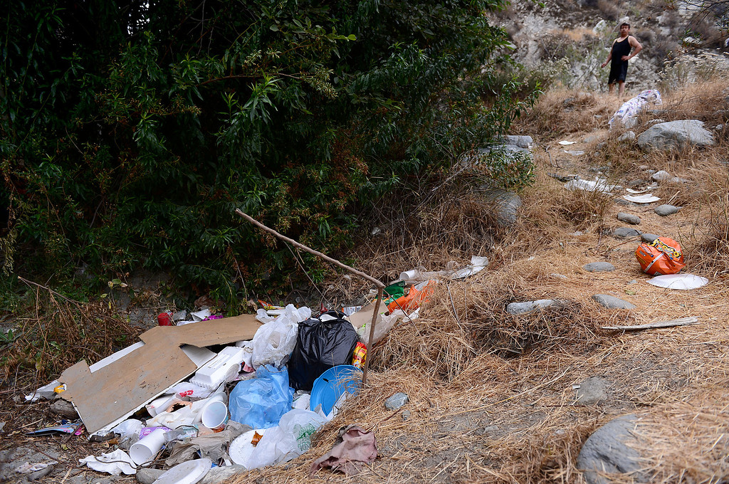 Description of . Gary Romo, of Los Angeles, is in disbelieve at the piles of garbage he found after crossing the San Gabriel River along the East Fork in the Angeles National Forest Saturday, July 20, 2013 during his first visit to the area. The Urban Conservation Corps is trying to educate visitors and campers on packing their trash out in orange bags they hand out and breaking down dams for pools to avoid trapping the Santa Ana Sucker, a small fish that is listed as threatened. (SGVN/Staff Photo by Sarah Reingewirtz)