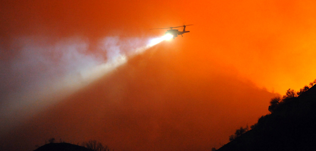 Description of . A Los Angeles County Fire Department water dropping helicopter pulls out of a canyon after making a night water drop to battle the Madre Fire in northwest of Highway 38 in Azusa on Monday September 23, 2013. (San Gabriel Valley Tribune/Staff Photo by Keith Durflinger)