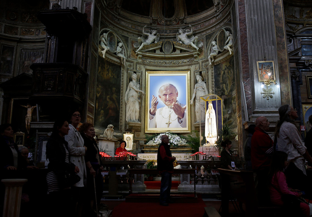 Description of . A portrait of late Pope John Paul II is displayed inside St. Sprit in Sassia church during a mass in Rome, Wednesday, April 23, 2014. Hundred thousands of pilgrims and faithful are expected to reach Rome to attend the scheduled April 27 ceremony at the Vatican in which Pope Francis will elevate in a solemn ceremony John XXIII and John Paul II to sainthood. (AP Photo/Gregorio Borgia)