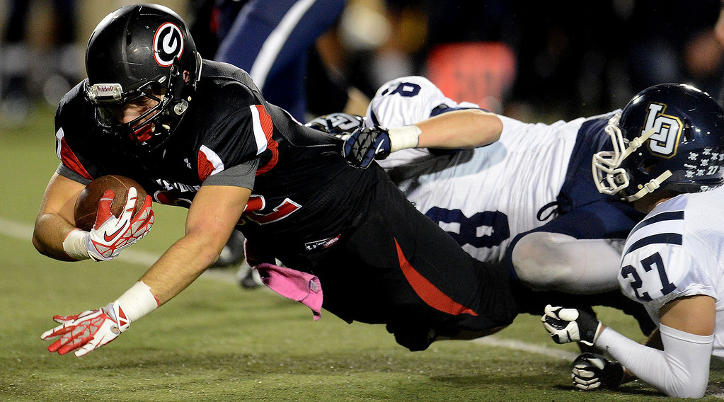 Description of . Glendora's Amin Raad (32) dives for a first down as Los Osos' Tyler Lyon (8) makes the tackle in the first half of a prep football game at Citrus College in Glendora, Calif., on Thursday, Oct. 31, 2013.    (Keith Birmingham Pasadena Star-News)