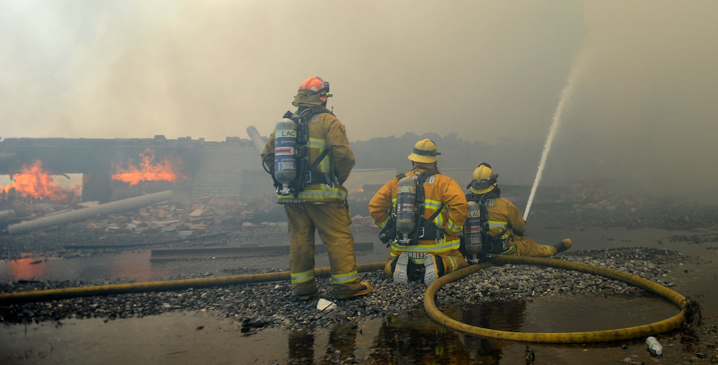 Description of . Los Angeles County firefighters battle a 3-alarm fire in heavy smoke at an abandoned warehouse near 9th Avenue and Clark Avenue on Tuesday, July 9, 2013 in City of Industry, Calif.  (Keith Birmingham/Pasadena Star-News)