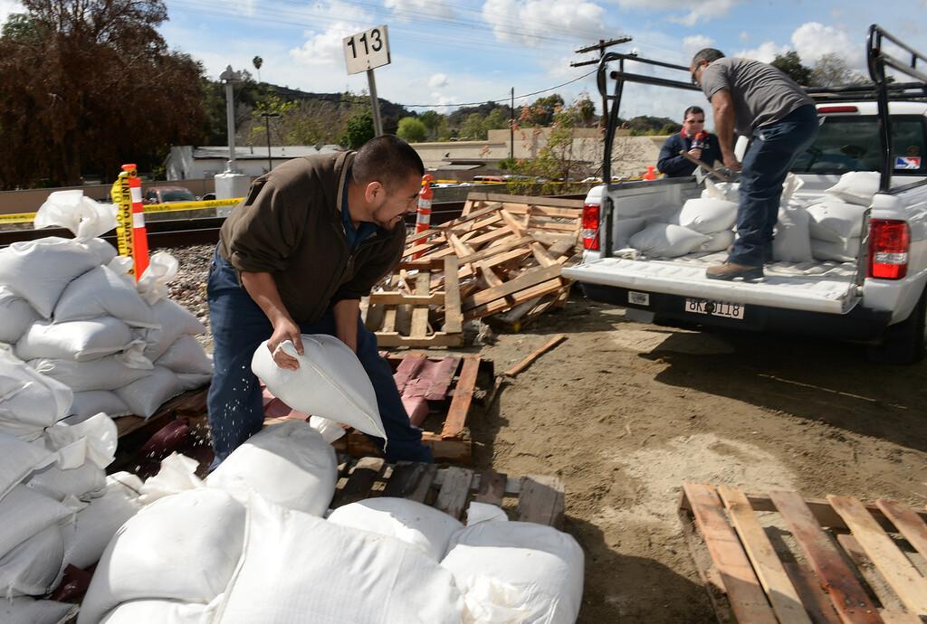 Description of . Filiberto Castaneda, left, and Eric Morones load up sandbags at the Glendora City Yard for St. Dorothy's School in Glendora on Thursday February 27, 2014. (Staff Photo by Keith Durflinger/San Gabriel Valley Tribune)