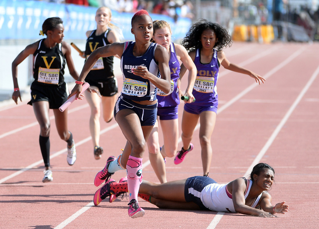 Description of . Redlands Juanita Webster, center, competes in the 1600 sprint medley seeded race during the Mt. SAC Relays in Hilmer Lodge Stadium on the campus of Mt. San Antonio College in Walnut, Calif., on Saturday, April 19, 2014. 