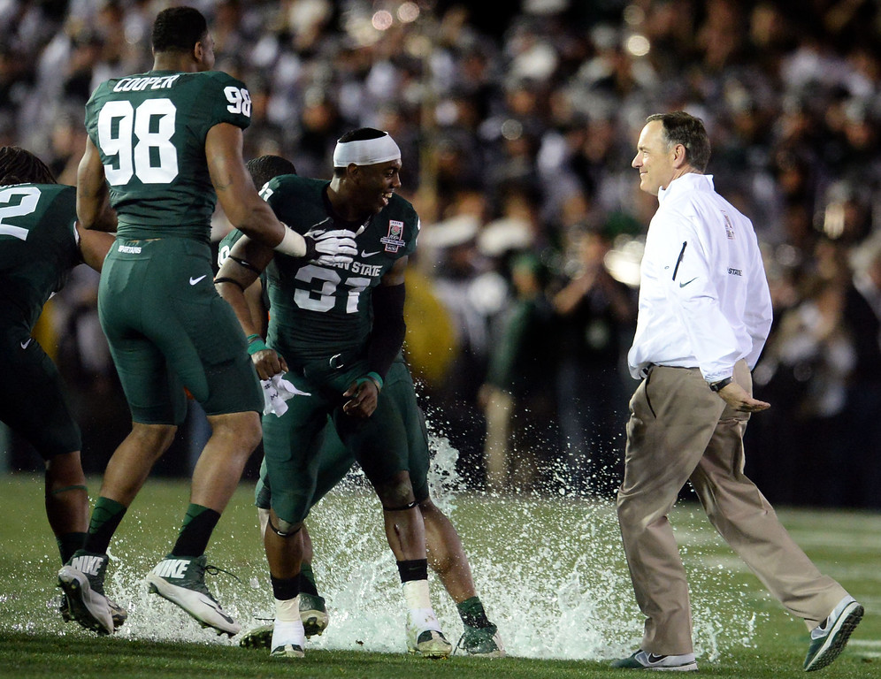Description of . Michigan State head coach Mark Dantonio, right, smiles after avoiding the gatorade bath after defeating Stanford 24-20 during the 100th Rose bowl game in Pasadena, Calif., on Wednesday, Jan.1, 2014. 