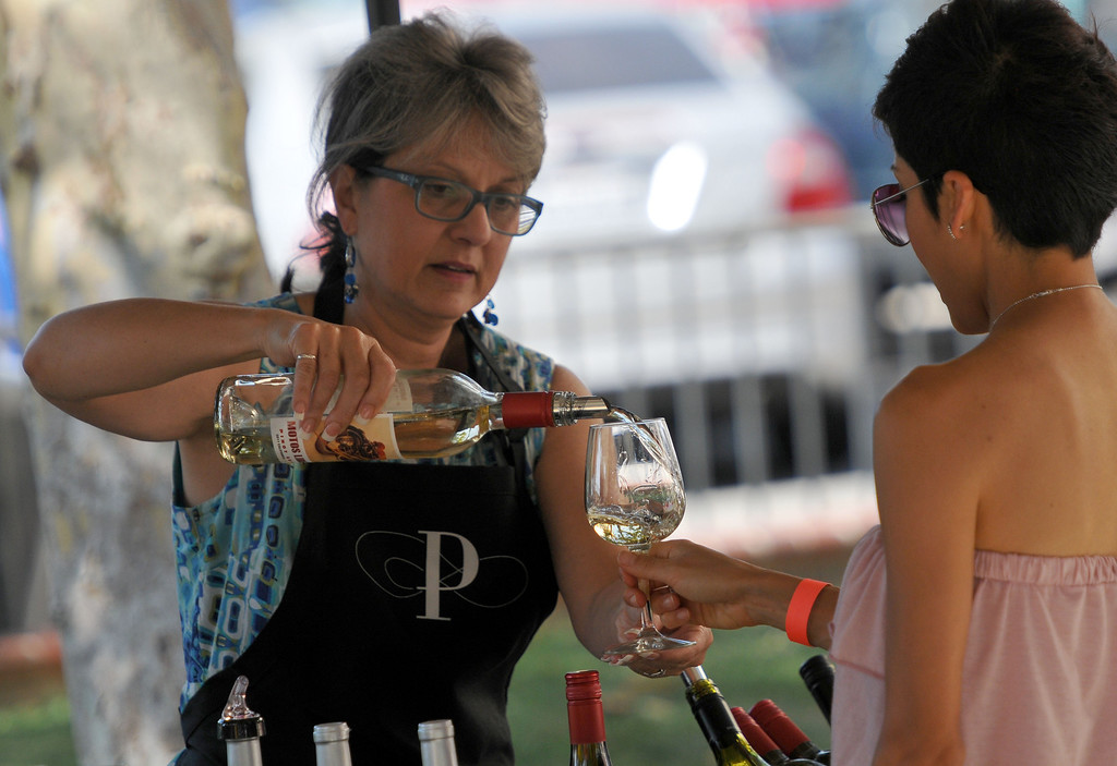 Description of . (John Valenzuela/ Staff Photographer)  Maria Clark of Paxton Cellars Winery pours a glass of wine during the Redlands Wine, Beer, and Music event at Ed Hales Park in downtown Redlands, Saturday, June 22, 2013.