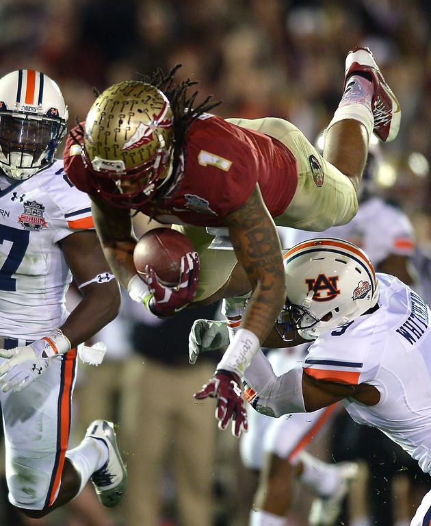 Description of . Florida State's Kelvin Benjamin is upended by Auburn's Jermaine Whitehead in the second half of the BCS national championship game at the Rose Bowl, Monday, January 6, 2014. (Photo by Michael Owen Baker/L.A. Daily News)