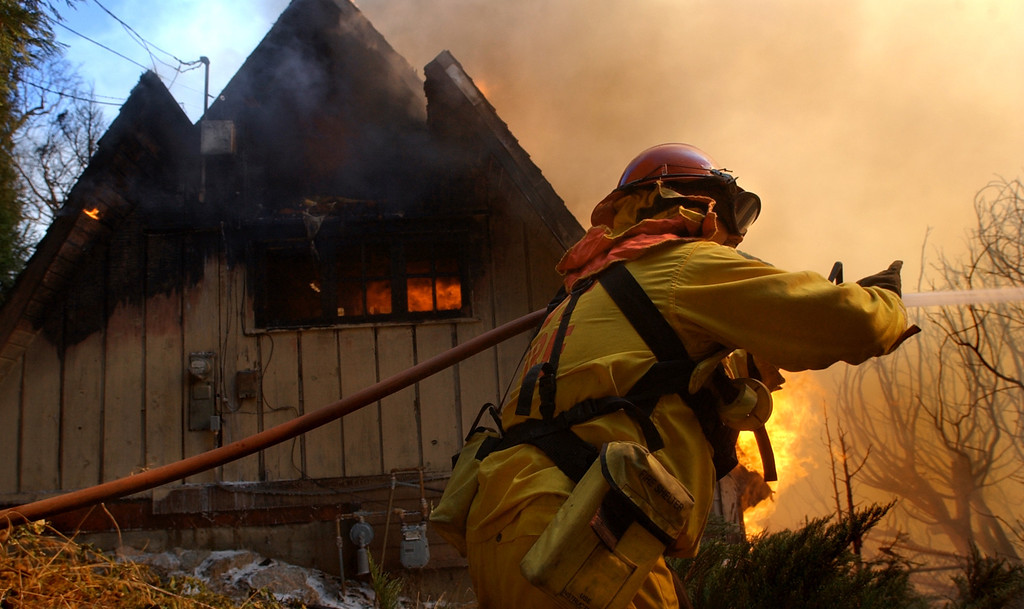 Description of . Ten years ago this month the arson caused Old Fire, fanned by Santa Ana winds burned thousands of acres, destroyed hundreds of homes and caused six deaths. The fire burned homes in San Bernardino, Highland, Cedar Glen, Crestline, Running Springs and Lake Arrowhead and forced the evacuation of thousand of residents. California Department of Forestry firefighter Eric Thompson of Susanville, Calif. defends one home while another burns during the