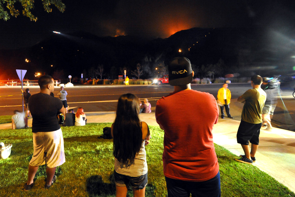 Description of . Residents and spectators watch as Los Angeles County Fire Department water dropping helicopters make night water drop to battle the Madre Fire in northwest of Highway 38 in Azusa on Monday September 23, 2013. (San Gabriel Valley Tribune/Staff Photo by Keith Durflinger)