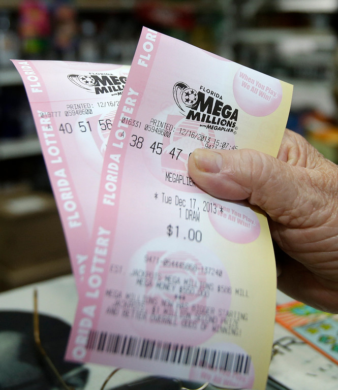 Description of . Tickets are purchased by a customer  Monday, Dec. 16, 2013, in Hialeah, Fla. The Mega Millions jackpot soared to $586 million on Monday amid a frenzy of ticket purchases, a jump that pushed the prize closer to the $656 million U.S. record set last year. (AP Photo/Alan Diaz)