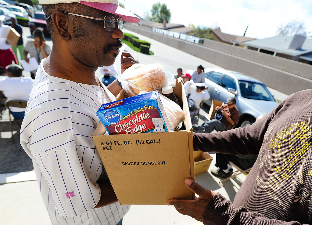 Description of . Rodolfo Talavera receives a free Thanksgiving dinner basket at 16th Street Seventh-day Adventist Church in San Bernardino on Tuesday, Nov. 26, 2013. The church distributed 175 baskets to families-in-need. (Photo by Rachel Luna / San Bernardino Sun)