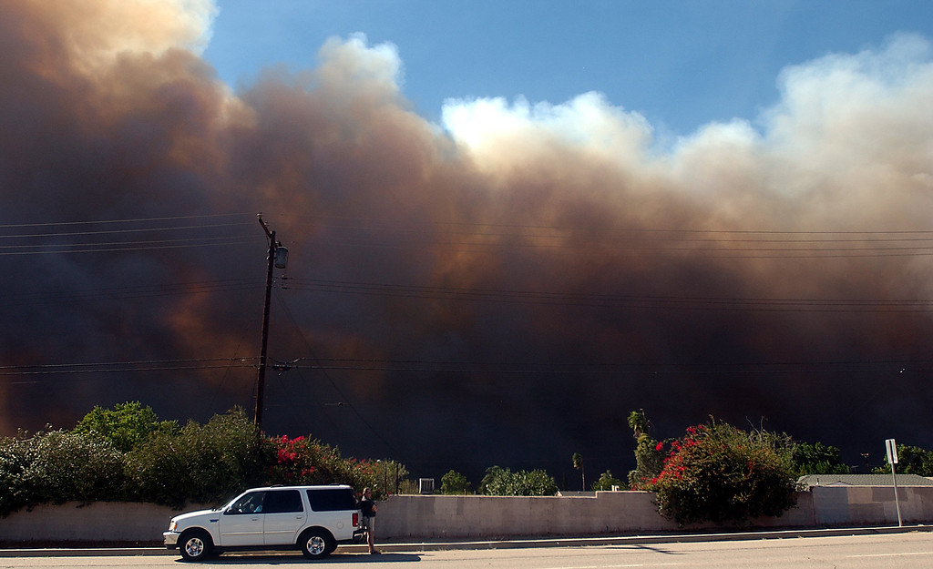 Description of . Ten years ago this month the arson caused Old Fire, fanned by Santa Ana winds burned thousands of acres, destroyed hundreds of homes and caused six deaths. The fire burned homes in San Bernardino, Highland, Cedar Glen, Crestline, Running Springs and Lake Arrowhead and forced the evacuation of thousand of residents. Butch Kempka, 55, of East Highlands Ranch, watches smoke travel along Sterling Avenue in San Bernardino. (Staff file photo/The Sun)