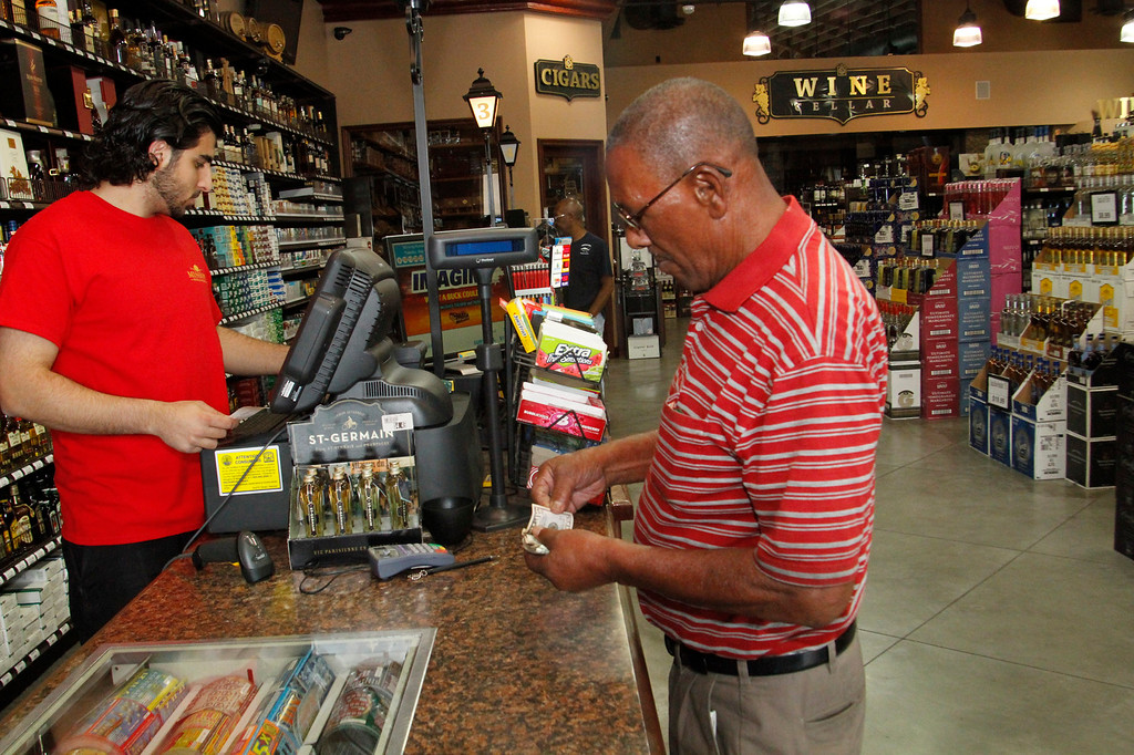 Description of . Arnold Tilman, of Pasadena, buys a Powerball ticket, a jackpot worth $600 milion, at Mission Liquor Store in Pasadena, Friday, May 17, 2013. (Correspondent Photo by James Carbone/SXCITY)