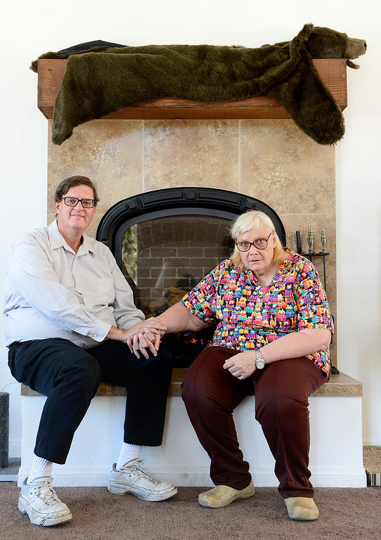 Description of . Jim Crabtree and his wife Rita Delehanty sit on the hearth of their gas furnace fireplace of their green home