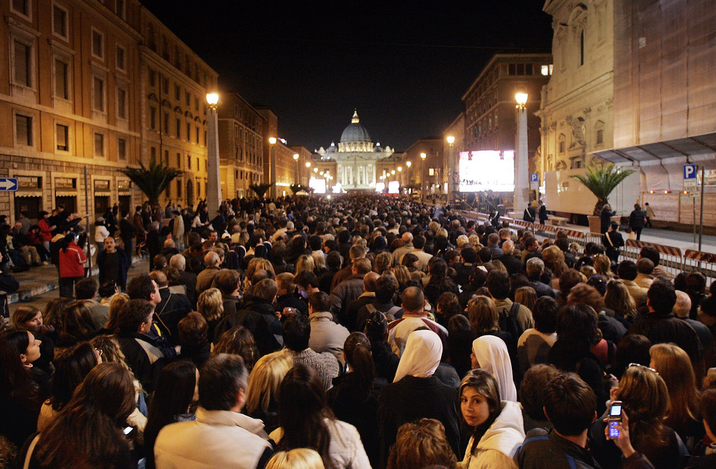 Description of . People fill Via Della Conciliazione boulevard about 950 meters (2900 feet) away from the facade of St. Peter's Basilica after  Pope John Paul II's body was carried across the square into the Basilica for public viewing,  at the Vatican Monday, April 4, 2005.  With tens of thousands of mourners outside hoping for a glimpse of the body, 12 pallbearers flanked by Swiss Guards carried the late pontiff's body on a crimson platform from the Sala Clementina, where it had laid in state since Sunday. (AP Photo/Luca Bruno)