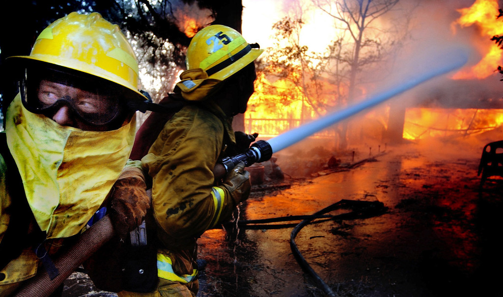 Description of . Ten years ago this month the arson caused Old Fire, fanned by Santa Ana winds burned thousands of acres, destroyed hundreds of homes and caused six deaths. The fire burned homes in San Bernardino, Highland, Cedar Glen, Crestline, Running Springs and Lake Arrowhead and forced the evacuation of thousand of residents. A firefighter, left, yells for more water as they try to stop a house fire from spreading to the trees in the wilderness of Crestline, on Sunday October 26, 2003 during the second day of the Old Fire. (Staff file photo/The Sun)