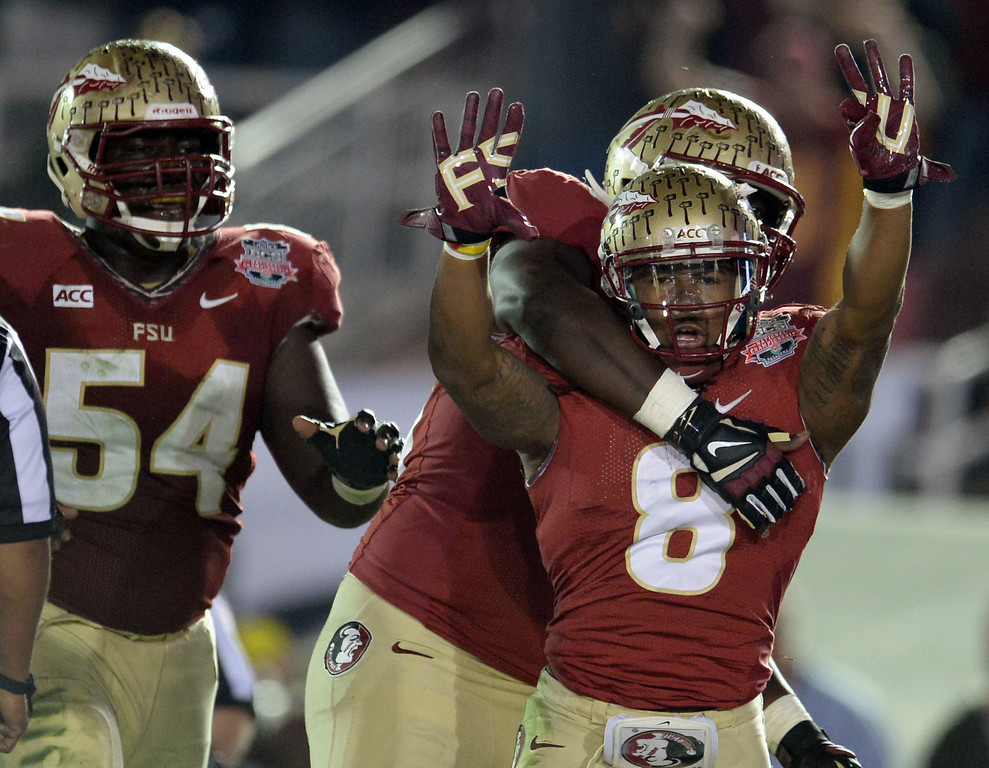 Description of . Florida State running back Devonta Freeman (8) reacts after running for a touchdown against Auburn in the first half of the BCS National Championship game at the Rose Bowl in Pasadena, Calif., on Monday, Jan. 6, 2014. 