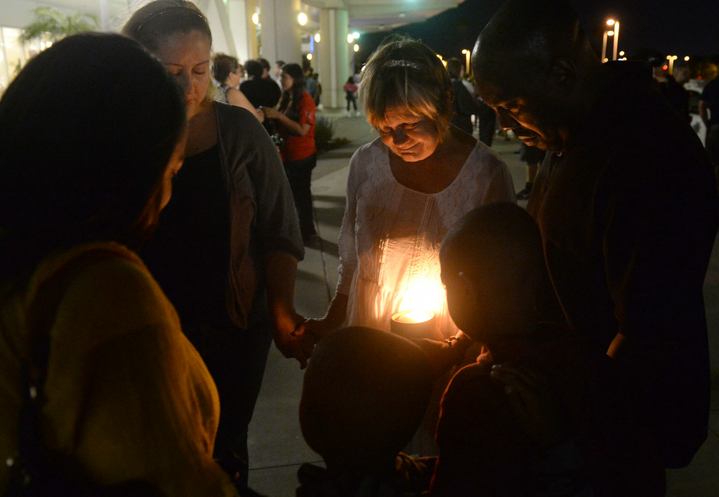 Description of . Margaret Avila prays with Jean Marie McAllister (L), retired San Bernardino Police officer Erick Grantley (R) and his family, during a vigil for wounded San Bernardino Police officer Gabriel Garcia in front of Arrowhead Regional Medical Center in Colton, Ca., Friday, August 22, 2014. Garcia is being treated at the hospital after he suffered  gunshot wounds to the upper torso during an early morning shoot out in San Bernardino. (Photo by John Valenzuela/ The Sun)