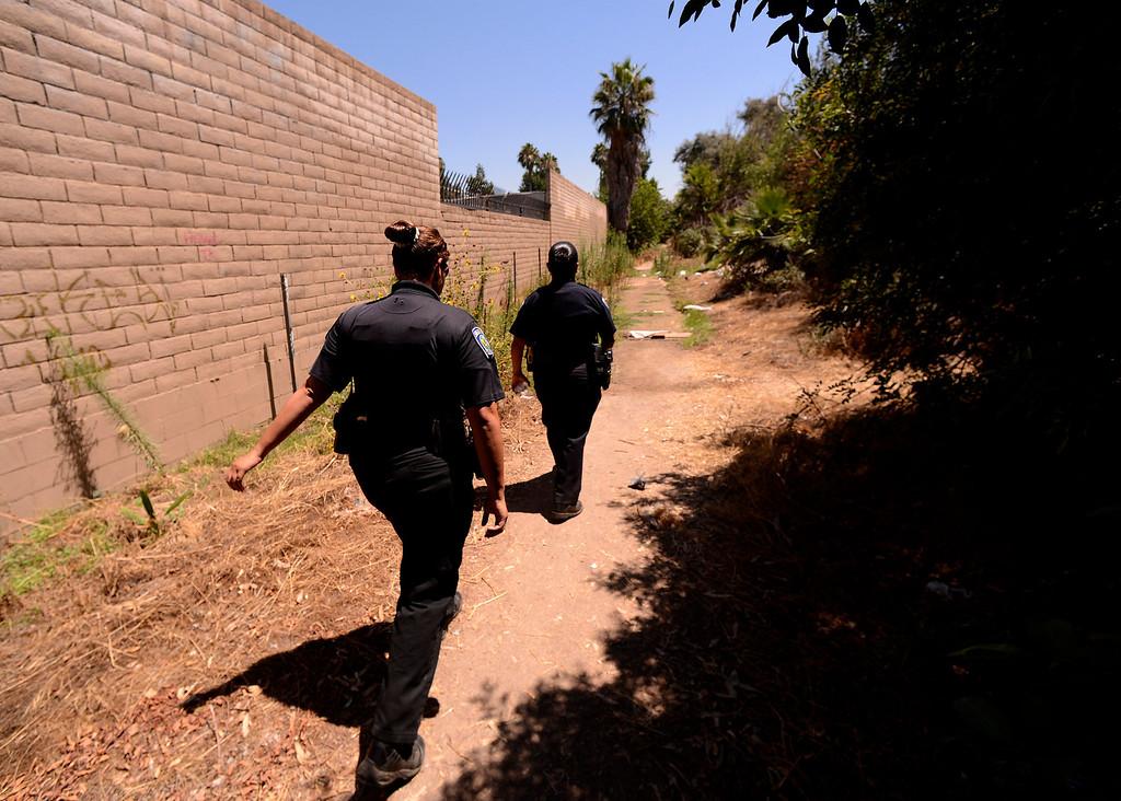 Description of . San Bernardino Police Officers Sochilt Martinez, left, and Araceli Mata, right, look for homeless camps along the I-210 freeway in San Bernardino August 14, 2013. GABREL LUIS ACOSTA/STAFF PHOTOGRAPHER.