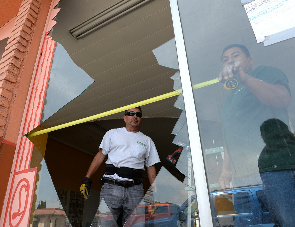 Description of . Martin Jimenez, left, and Daniel Bonilla measure a broken front window of a former tile store after the 5.1 earthquake centered in La Habra on Saturday March 29, 2014. (Staff Photo by Keith Durflinger/Whittier Daily News)