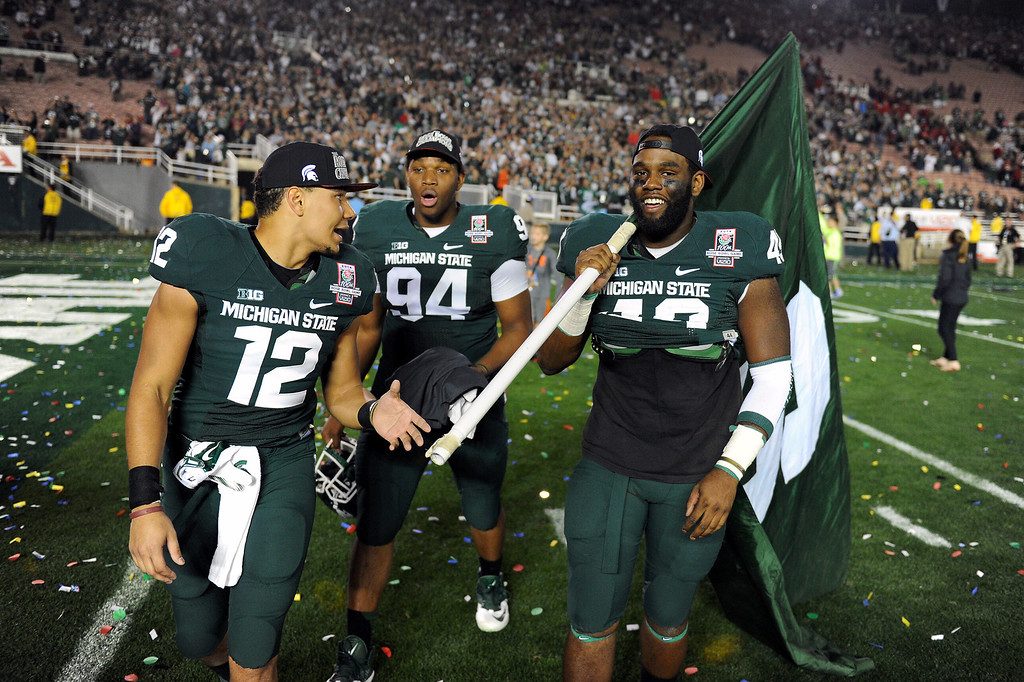 Description of . Michigan State players walk the field after beating Stanford 24-20 at the Rose Bowl, Wednesday, January 1, 2014. (Photo by Michael Owen Baker/L.A. Daily News)