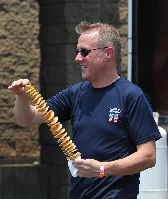 Description of . (John Valenzuela/Staff Photographer) Beau Yarbrough of Redlands walks with his order of spiral potatoes from the during the second annual Food Truck and Brewfest in Redlands Saturday, June 29, 2013.