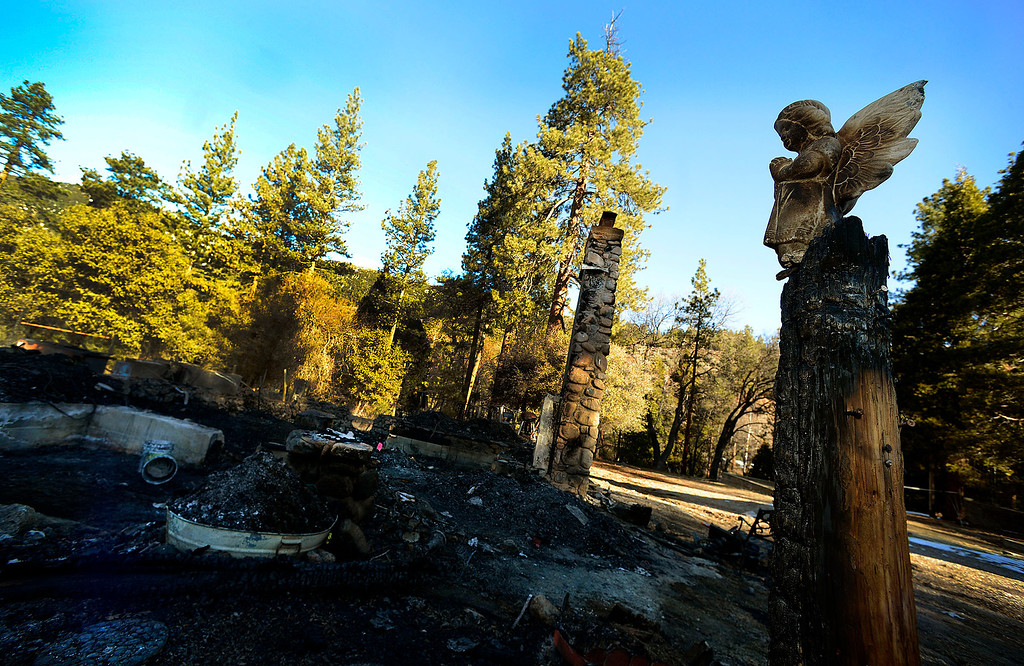Description of . A ceramic angel statue overlooks the burned out cabin which is all that remains of fugitive Christopher Dorner's last stand in Seven  Oaks February 15, 2013.   (Photo by Gabriel Luis Acosta/The Sun)