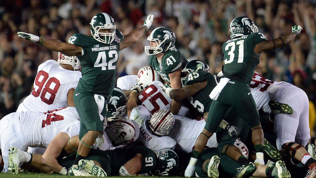 Description of . Michigan State linebacker Kyler Elsworth (41), center, looks-up after stopping Stanford on 4th and 1 in the fourth quarter as his teammates react during the 100th Rose bowl game in Pasadena, Calif., on Wednesday, Jan.1, 2014. Michigan State won 24-20.