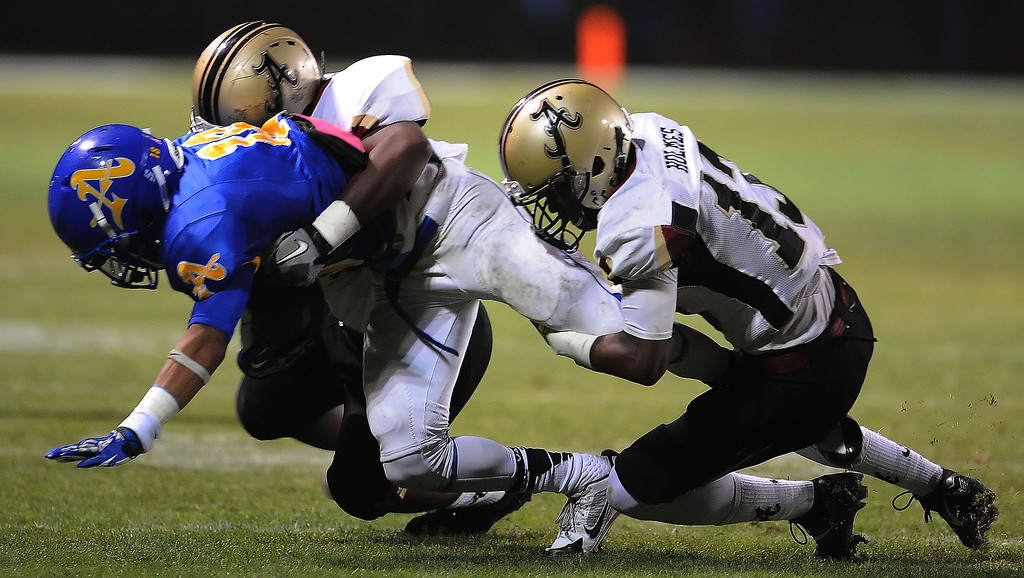 Description of . Bishop Amat's Trevon Sidney is tackled by the Alemany defense in the first half of a prep football game at Bishop Amat High School in La Puente, Calif., on Friday, Oct. 25, 2013.    (Keith Birmingham Pasadena Star-News)