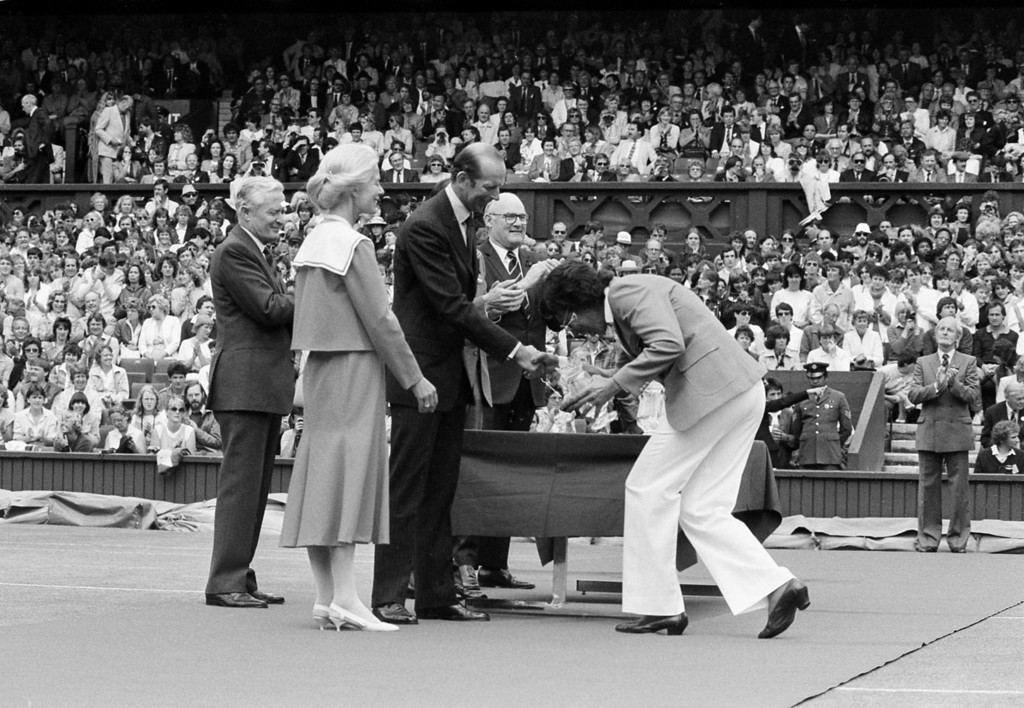 Description of . Althea Gibson, of United States, curtsies before the Duke of Kent, president of the All England Lawn Tennis Club, on Center Court during a ceremony to mark the centennial year of the Ladies\' Championships at Wimbledon, England, July 2, 1984.  Gibson, a former professional golfer, became the first black person to win the Wimbledon title in 1957.  Standing second from left is the Duchess of Kent.  (AP Photo)