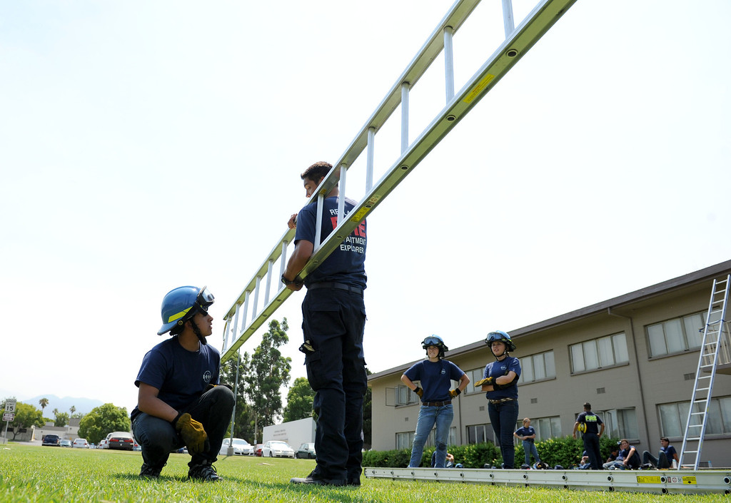 Description of . (John Valenzuela/Staff Photographer)  U.S Forest Firefighter Matt Ambriz shows Marllon De La Cruz 18, of Redlands the proper technique for picking up a ladder during the Redlands Emergency Services Academy ladder training, Thursday, July 18, 2013.