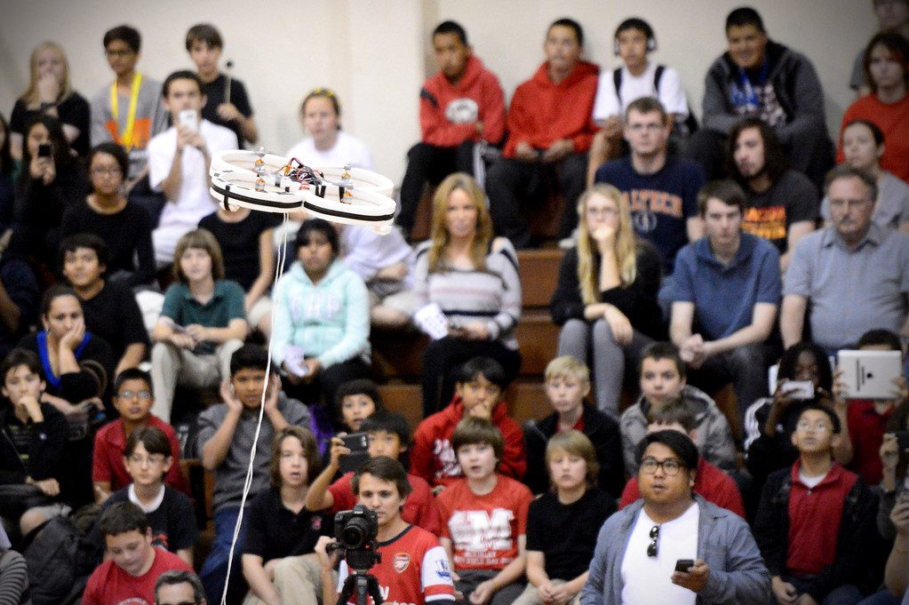Description of . A quad copter flies as a crowd of school children watch mechanical engineering Caltech students compete in the annual ME72 Engineering Design Contest at the Pasadena campus Tuesday, March 11, 2014. The goal in