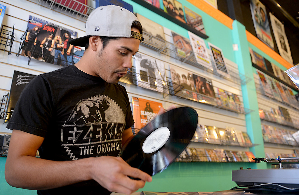 Description of . Mauricio Morgan, 26, says, listening to music all day, is just one of the benefits working the counter at Redlands second store offering vinyl records. Redlands Vinyl Records and Collectibles recently opened its doors in Redlands to offer a second place in town to collect records and other collectibles.  (Photo by Rick Sforza/Redlands Daily Facts)