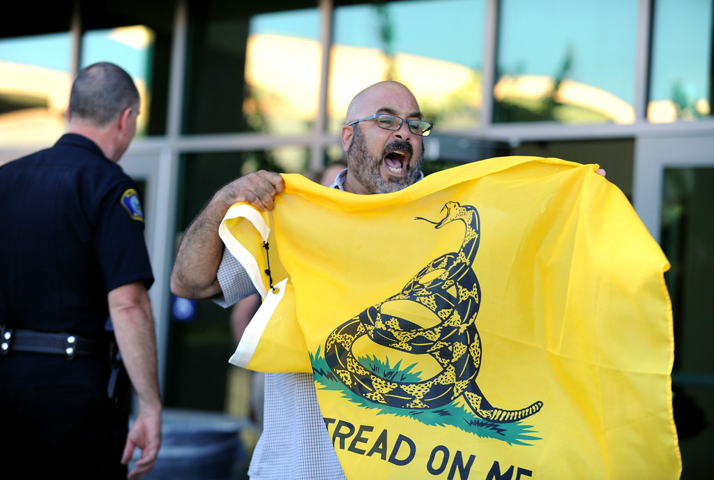 Description of . A man yells after being denied taking a flag into a town hall meeting on Wednesday, July 2, 2014 at Murrieta Mesa High School in Murrieta, Ca. The meeting is being held in response to immigrants who were being processed through a Texas Border Patrol Station and delivered to the Murrieta Border Patrol Station on Tuesday, which created protests from both sides of the immigration issue. (Micah Escamilla/The Sun)