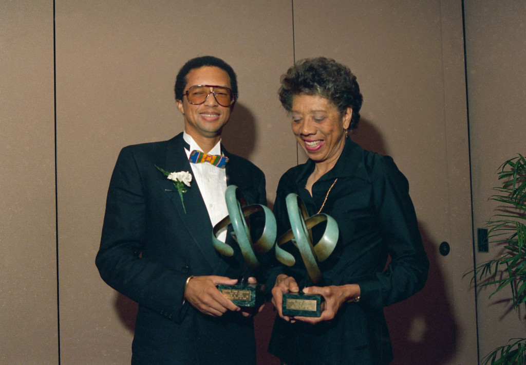 Description of . Tennis players Arthur Ashe, left, and Althea Gibson pose while holding trophies after being inducted into the Eastern Tennis Association Hall of Fame, May 13, 1988 at the Marriott Marquis in New York.  (AP Photo/Susan Ragan)