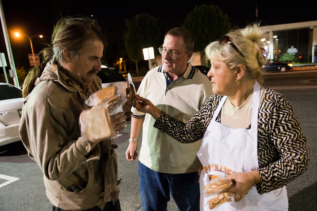 Description of . Paul McQuown, who is homeless, receives sandwiches and a hot soup from Nicolette Wingert, right, and Phillip Stern in Glendora on Wednesday night, Nov. 27, 2013. Nicolette Wingert has been feeding the homeless six days a week for the past seven years with Nurses4Christ, a nonprofit organization she founded in 2006. She and Phillip Stern of Glendora have been going every day since 2008, feeding homeless people sandwiches and hot food; giving them bottles of water, clothes and blankets. (Photo by Watchara Phomicinda/San Gabriel Valley Tribune)