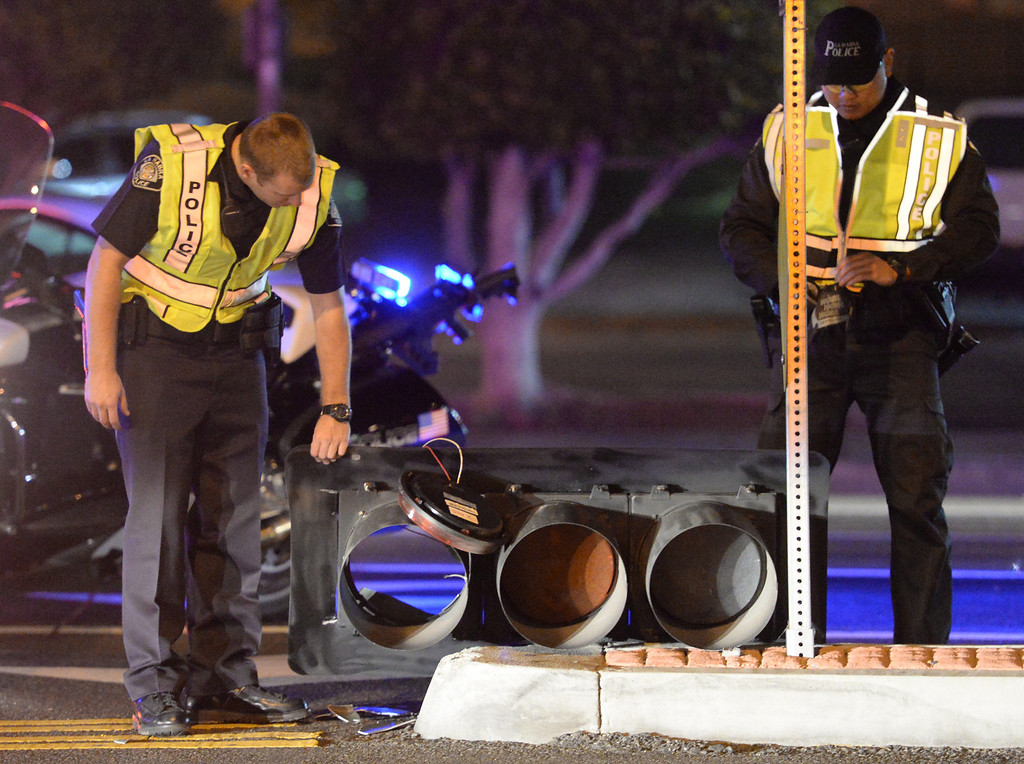 Description of . La Habra Police officers prepare to carry off a traffic signal that fell on traffic lanes at the intersection of Beach Boulevard and Lambert Road after the 5.1 earthquake in La Habra on Friday March 28, 2014. (Staff Photo by Keith Durflinger/Whittier Daily News)