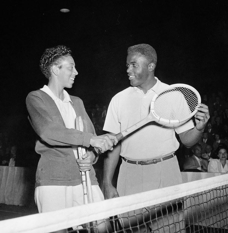 Description of . Brooklyn Dodgers\' second baseman, Jackie Robinson, gets tennis tips from tennis star Althea Gibson at the celebrity tennis tournament at the 7th Regiment Armory in New York, Feb. 16, 1951.  The tournament was staged for the benefit of the American National Theater and Academy.  (AP Photo/Marty Lederhandler)