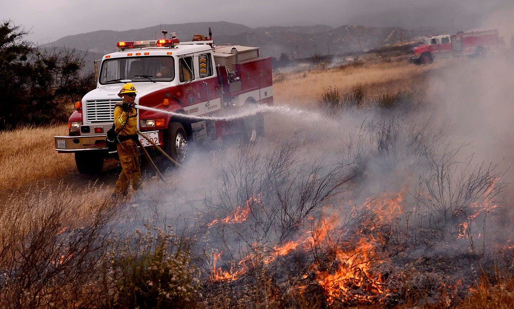 Description of . A firefighter hoses down a section of burning vegetation during a training fire along Sierra Avenue north of Summit Avenue in North Fontana May 23, 2013.   GABRIEL LUIS ACOSTA/STAFF PHOTOGRAPHER.