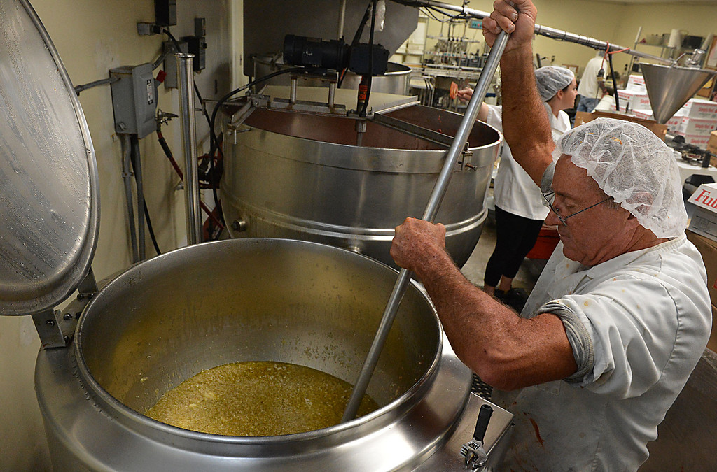 Description of . Gary Hummel stirs a cooking batch of olive oil, onions and garlic while cooking Saverino's Marinara Sauce at Da'Kine Foods in Newport Beach. Following the successful launch of Saverino's Italian Deli and Market in Redlands nearly two years ago, David Saverino is bottling the flavor of his business with the introduction of four separate sauces. In addition to selling the sauces at his deli, Saverino hopes to see his product on the shelves of local markets. (Photo by Rick Sforza/Redlands Daily Facts)