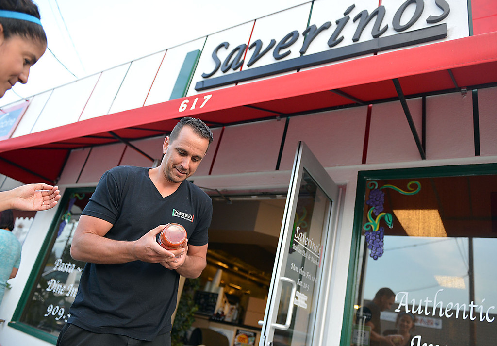 Description of . David Saverino outside his Redlands' restaurant, with his wife Veronica, after he returned from the bottling process in Newport Beach Thursday May 8, 2014 with his first batch of bottled sauces.  Following the successful launch of Saverino's Italian Deli and Market in Redlands nearly two years ago, David Saverino is bottling the flavor of his business with the introduction of four separate sauces. In addition to selling the sauces at his deli, Saverino hopes to see his product on the shelves of local markets. (Photo by Rick Sforza/Redlands Daily Facts)