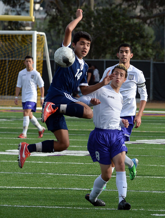 Description of . Baldwin Park's Eric Garces (14) goes up high for the ball past Diamond Bar's Guy Horcasitas (8) in the first half of a CIF-SS quarterfinal prep playoff soccer match at Diamond Bar High School in Diamond Bar, Calif., on Thursday, Feb.27, 2014. Baldwin Park won 2-1. (Keith Birmingham Pasadena Star-News)