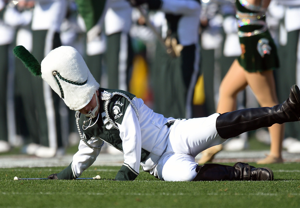 Description of . The Michigan State Marching Band drum major loses his footing and takes a spill while performing before the Rose Bowl game, Wednesday, January 1, 2014. (Photo by Michael Owen Baker/L.A. Daily News)