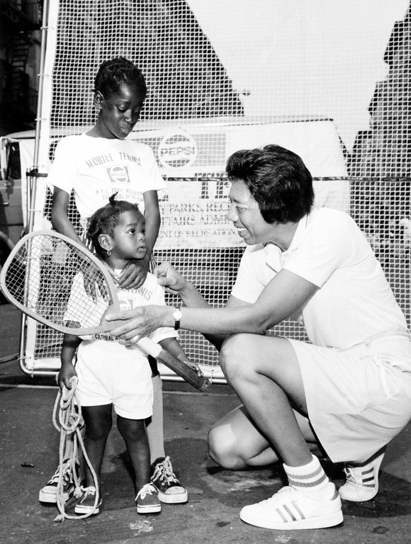 Description of . Tennis player Althea Gibson shows the first tennis racket she used in 1942 on the streets of Harlem to Tiny Huston, 9, and her sister Monica, 1, in New York City, July 11, 1973.  Gibson opened the Pepsi-Cola summer tennis program which will bring the sport to 20,000 inner city youth.  (AP Photo)