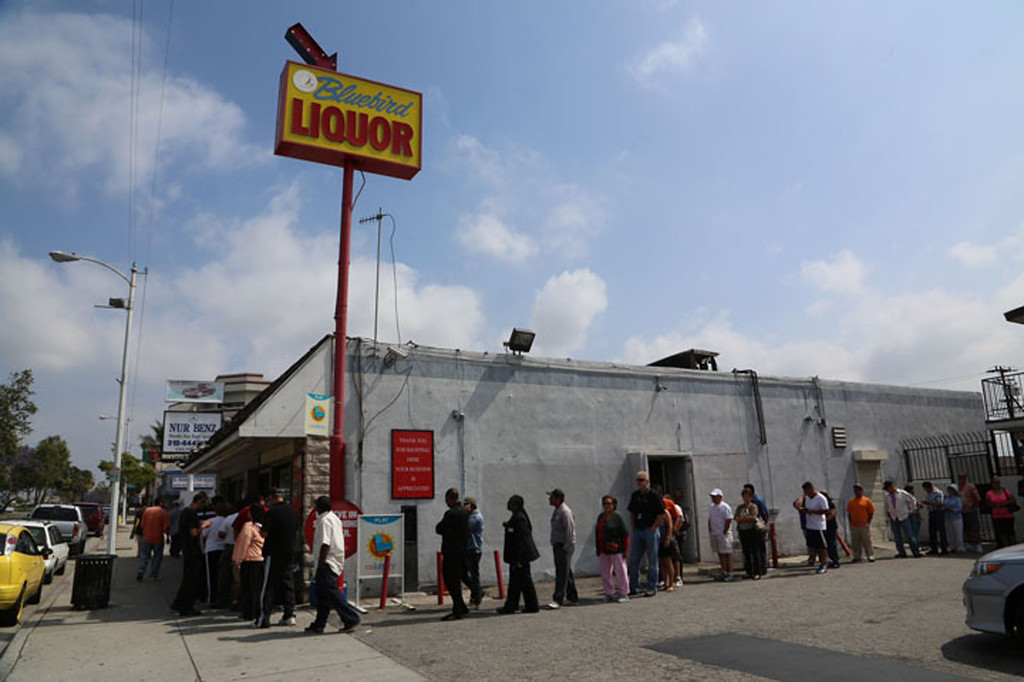 Description of . People line up to buy lottery tickets at the Bluebird Liquor store in Hawthorne on Friday. Saturday's jackpot is expected to reach near $600 million. (Chuck Bennett/Staff Photographer)