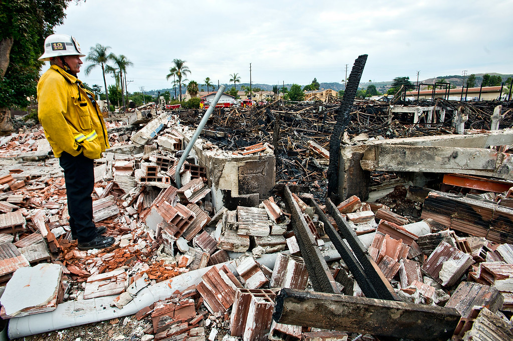 Description of . Battalion Chief Mike Leckliter looks over the debris of a destroyed warehouse after a 3-alarm fire near 9th Avenue and Clark Avenue in City of Industry on Wednesday, July 10, 2013. (SGVN/Staff Photo by Watchara Phomicinda)