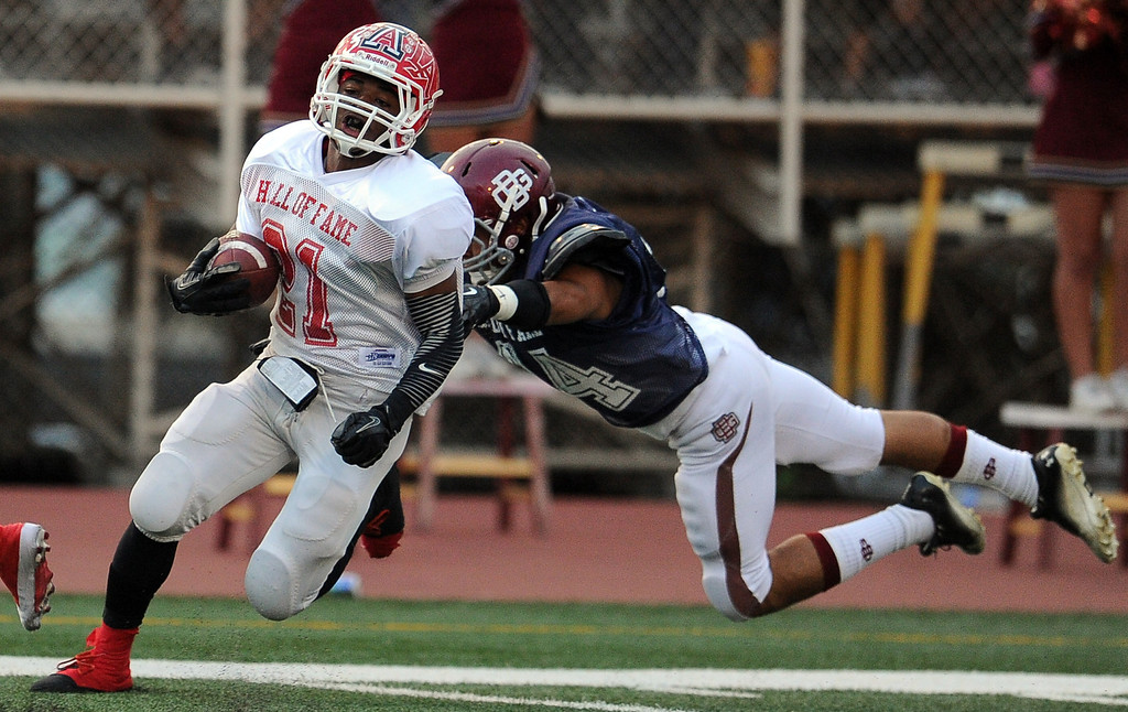 Description of . Eest's Aaron Vaughns (21) (Charter Oak) runs for a 54 years touchdown past West's Christopher Mendoza (Bell Gardens) in the first half of the annual East vs. West San Gabriel Valley Hall of Fame all-star football game at West Covina High School on Friday, May 17, 2013 in West Covina, Calif. 