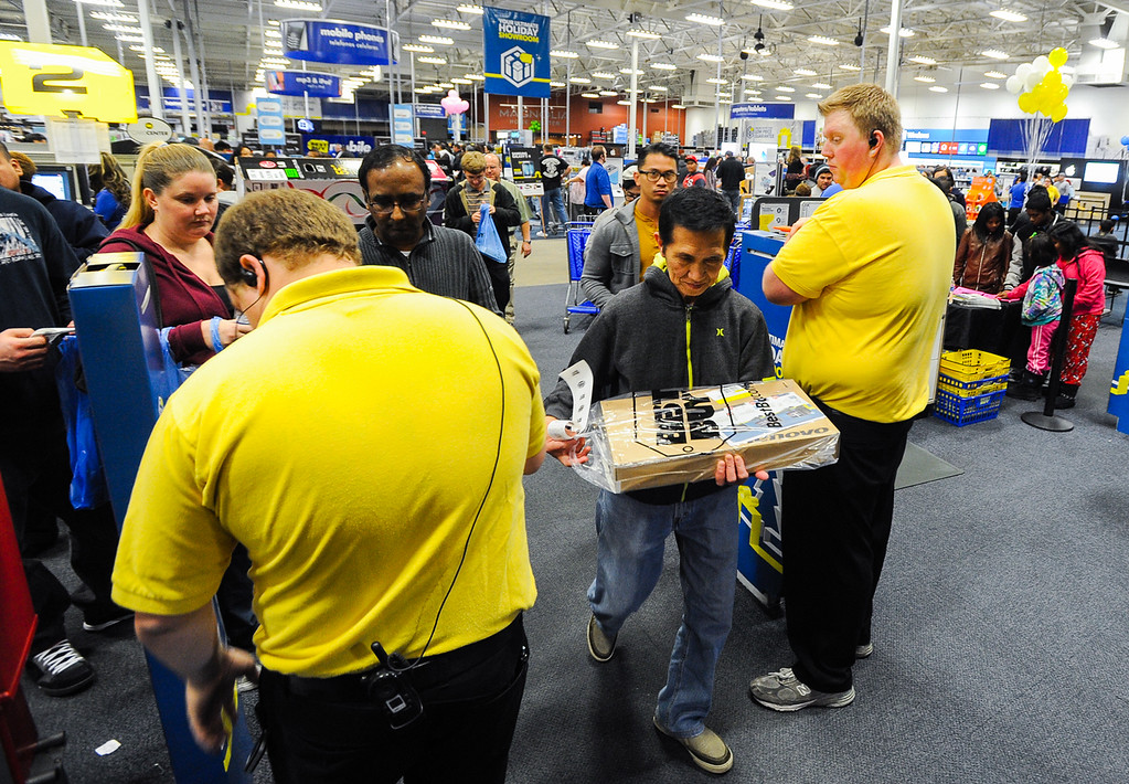 Description of . Shoppers leave Best Buy with early Black Friday deals after the store opened its doors at 6 p.m. for early sales on Thanksgiving in San Bernardino on Thursday, Nov. 28, 2013. Many retail stores pushed the boundary the Black Friday tradition this year with offering Black Friday deals on Thanksgiving day. (Photo by Rachel Luna / San Bernardino Sun)