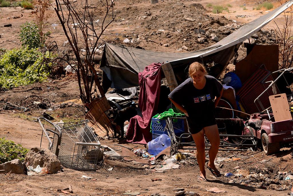 Description of . Dawna Bonner, 30, emerges from a homeless camp in a vacant lot along Ninth Street in San Bernardino August 14, 2013. GABREL LUIS ACOSTA/STAFF PHOTOGRAPHER.